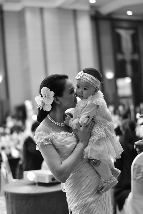 Khác với đám cưới của ba mẹ tại TP HCM, cô bé đã dạn dĩ hơn, không còn khóc nhè khi thấy đông người. Trong ảnh bé được mẹ Trang Nhung cưng nựng.