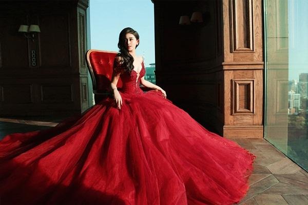 Chiếc đầm đầu tiên mang gam màu chủ đạo đỏ thẫm với phần chất liệu voan, lụa được xử lý kỹ càng nhằm mang đến vẻ bồng bềnh, sang trọng cho bộ trang phục.