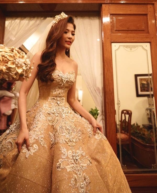 Thúy Diễm chia sẻ, cô từng ao ước có đám cưới như cổ tích, ở đó nữ diễn viên hóa thân thành công chúa xinh đẹp. Bộ váy màu đồng đính kết ren đá, pha lê tinh xảo, sử dụng các họa tiết cổ điển rơi dần từ ngực áo. Kiểu xếp ly cứng giữ cho dáng váy xòe rộng tôn vẻ lộng lẫy, sang trọng cho cô dâu trong hôn lễ.