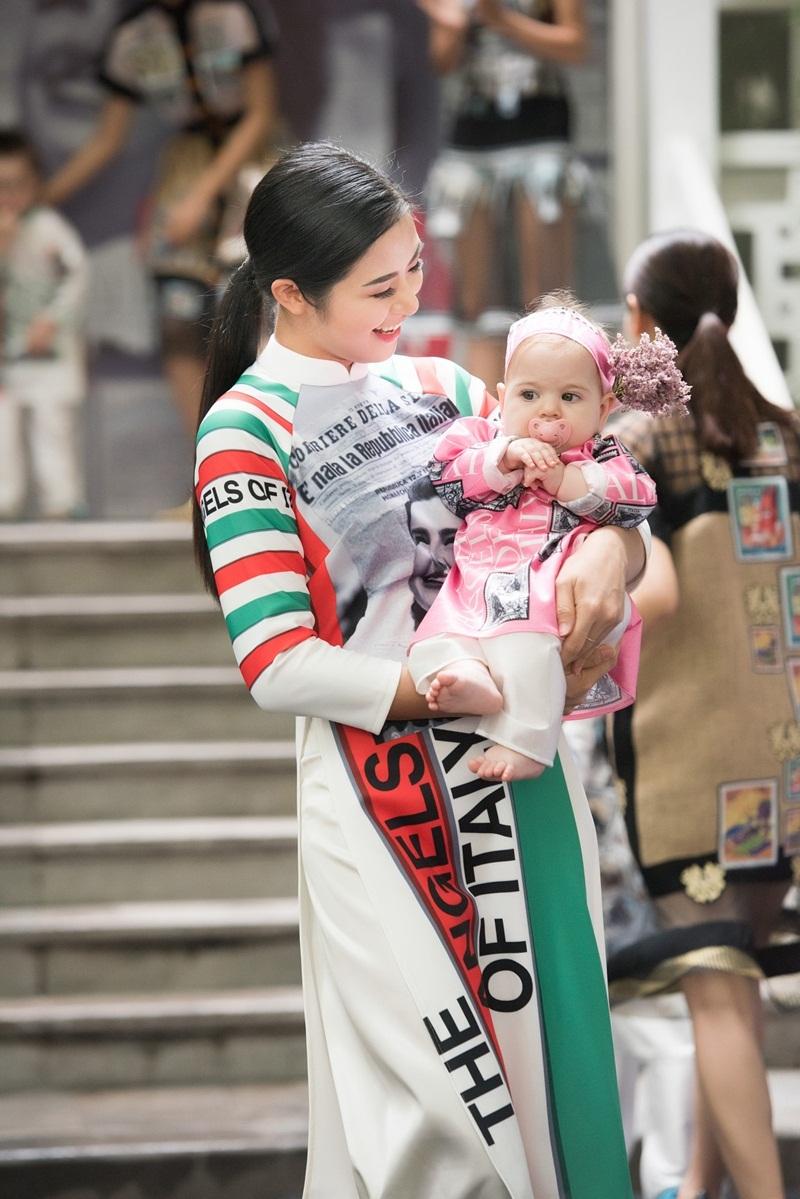 Hoa hậu gây chú ý khi bế trên tay một em bé sơ sinh người Ý được mặc áo dài hồng, thắt nơ rất xinh.