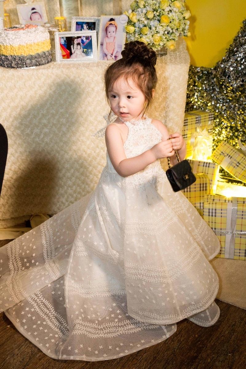 Phần váy dài tạo nên vẻ ngoài đáng yêu và độc đáo cho cô bé. Sự giống nhau không chỉ ở trang phục đôi, mà còn ở cách búi tóc cao và phụ kiện túi xách.