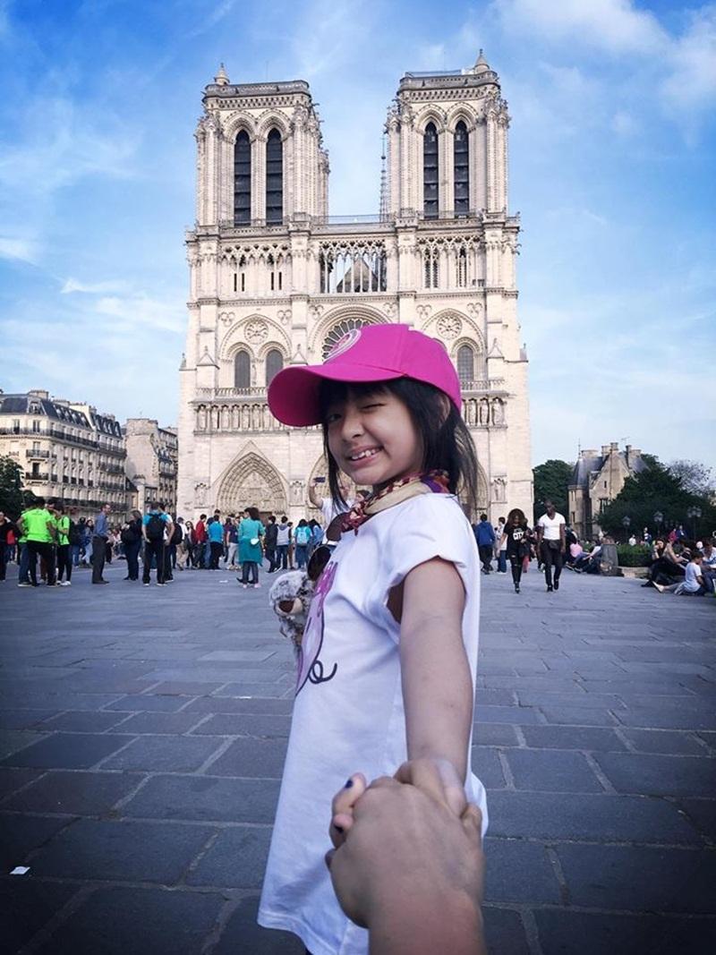 """Bé Bông thích thú chụp ảnh nắm tay theo phong cách """"Theo bông đi khắp thế gian"""" tại các địa điểm du lịch nổi tiếng như: tháp Eiffel, Khải Hoàn Môn, Nhà thờ Đức Bà Paris,…"""