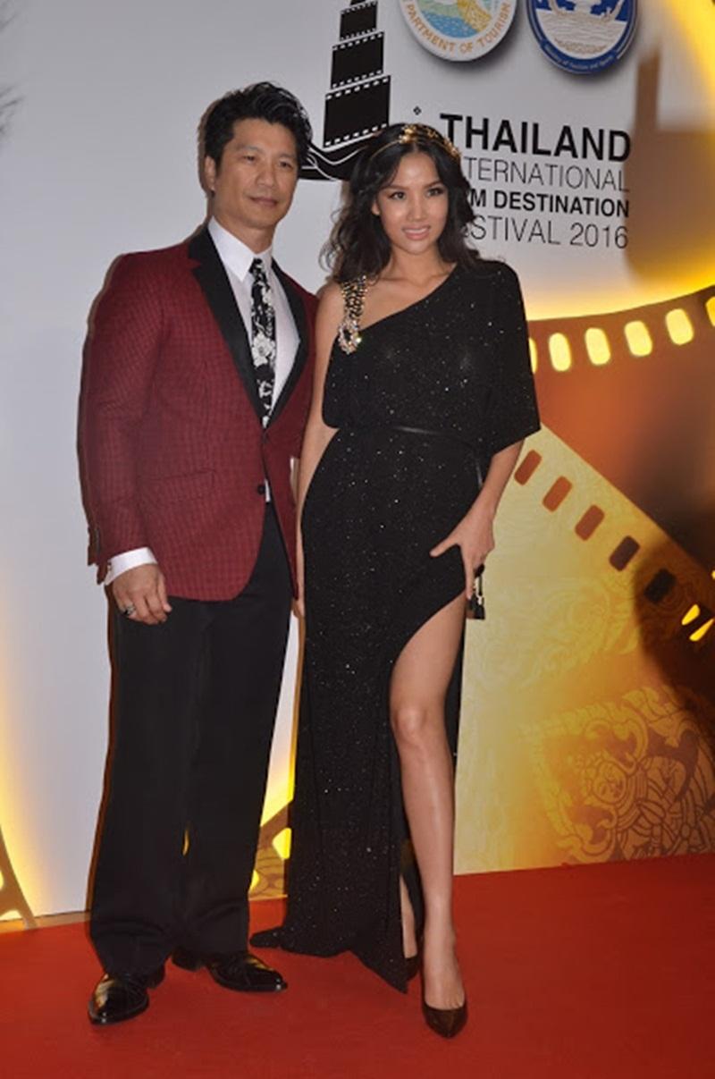 Diễn viên Bebe Phạm diện trang phục váy dạ hội xẻ cao khoác tay ông xã bước vào thảm đỏ.