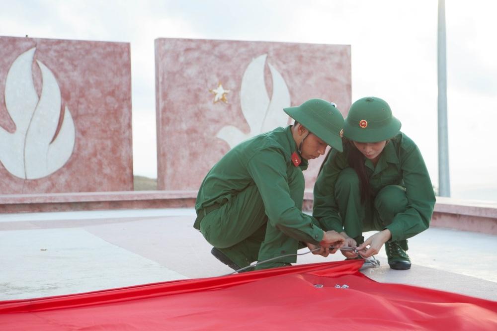 Thí sinh Hoa hậu Việt Nam cùng người chiến sĩ nâng niu lá cờ Tổ quốc.