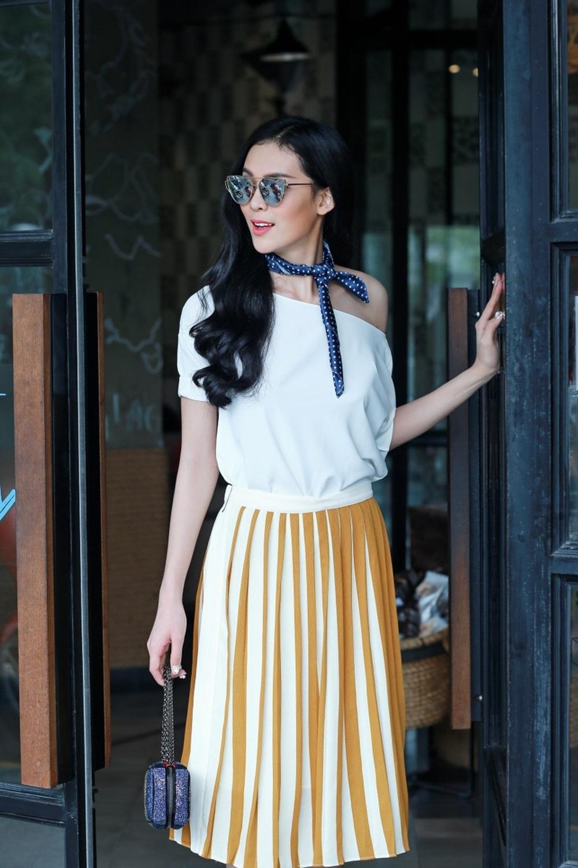 Trong ảnh dáng váy xếp ly xòe được may trên nền vải màu vàng tươi mix với áo lệch vai giúp người mẫu khoe làn da trắng rạng rỡ.