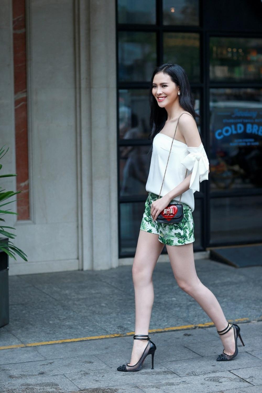 Áo trắng phom dáng rộng được mix khéo léo với quần short họa tiết lá cây cùng túi xách và giày mang đến nét mới mẻ đầy hiện đại.