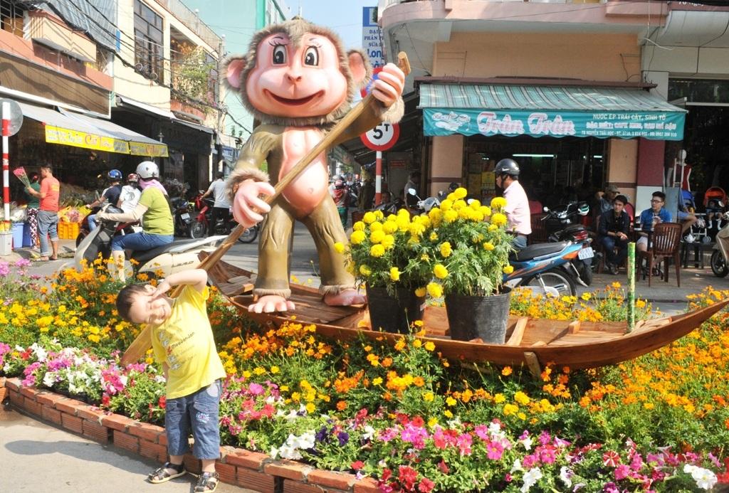 Một bé trai tạo dáng bên chú khỉ chèo xuồng...