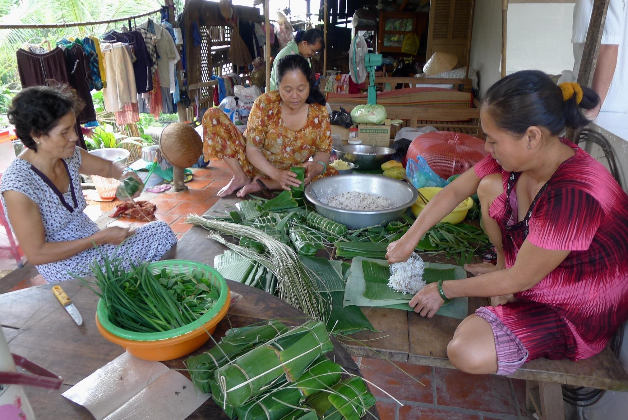 Gia đình bà Nguyễn Thị Kim Đồng cùng người thân gói bánh tét.
