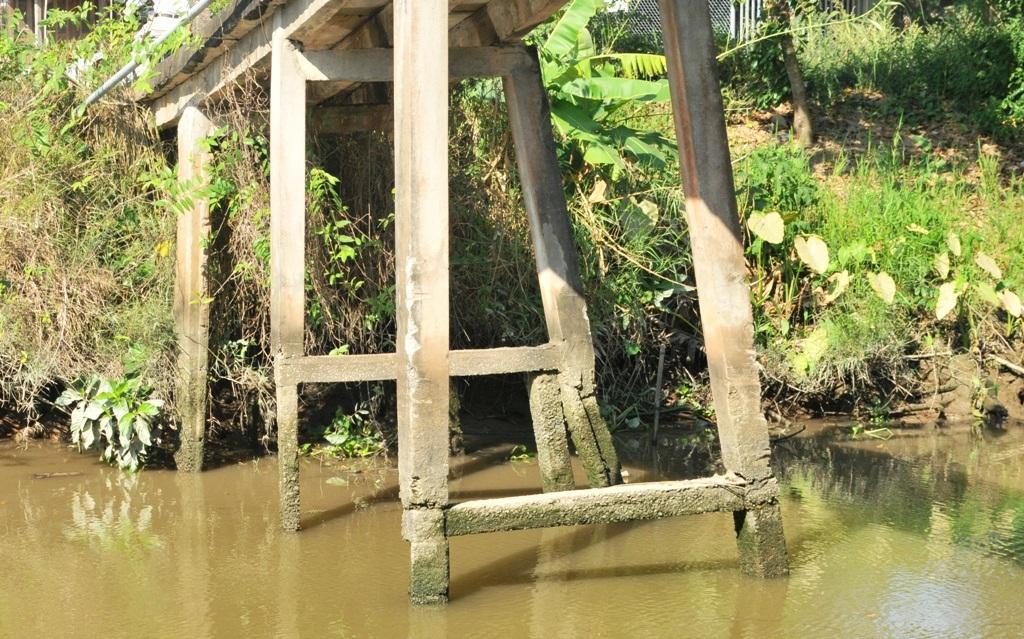 Một số trụ cầu bị gãy được gia cố thêm, số còn lại bị nước bào mòn nay chỉ to bằng cẳng chân người