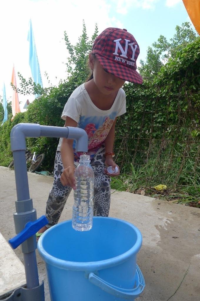Cháu Dương Kim Tuyến - lớp 2 Trường tiểu học Nam Thái A nhanh nhẹn lấy chai hứng đầy nước mang về cho mẹ xem sự thần kỳ của chiếc máy khi biến nước ngọt mặn thành nước ngọt và có thể uống ngay!