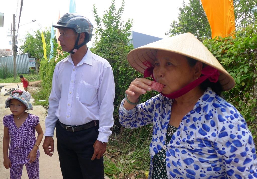 Bà Nguyễn Thị Thu - ấp Bảy Biển, xã Nam Thái A múc nước uống thử từ máy lọc và cho biết nước rất ngọt. Từ nay bà con đỡ khổ lắm.
