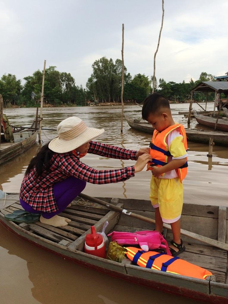 Chị T. cẩn thận mặc áo phao cho con trước khi vượt sông về nhà. Theo chị T., bên kia sông là đất Campuchia nhưng hầu hết là người Việt sinh sống nên hàng ngày nhu cầu qua lại con sông này là rất nhiều, nhất là các cháu học sinh.