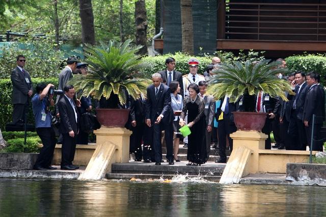 Tổng thống Obama ấn tượng về cuộc đi bộ thăm nhà sàn, ao cá Bác Hồ cùng Chủ tịch Quốc hội Nguyễn Thị Kim Ngân (Ảnh: Quý Đoàn).