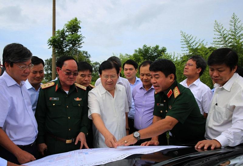 Phó Thủ tướng Trịnh Đình Dũng (giữa) cùng Trung tướng Võ Văn Tuấn (thứ 2 từ phải sang) kiểm tra thực địa khu vực dự kiến mở rộng sân bay Tân Sơn Nhất.