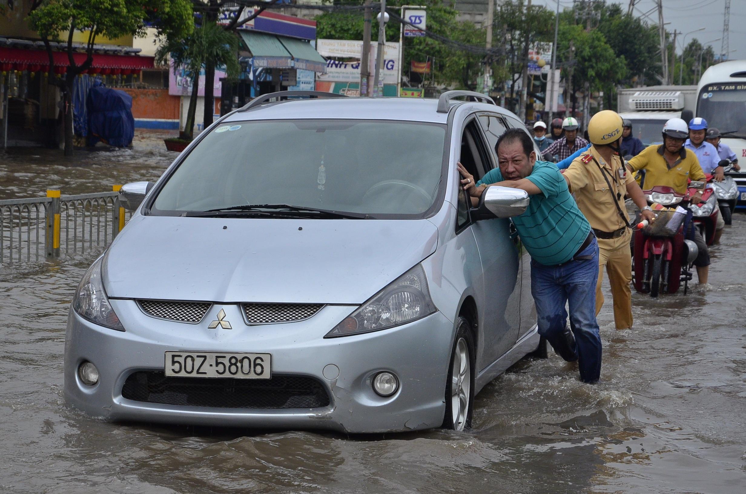 Nhiều xe ô tô chết máy giữa đường giống xe máy. Trong ảnh: Chủ xe cố gắng đẩy chiếc xe ra khỏi con đường ngập úng