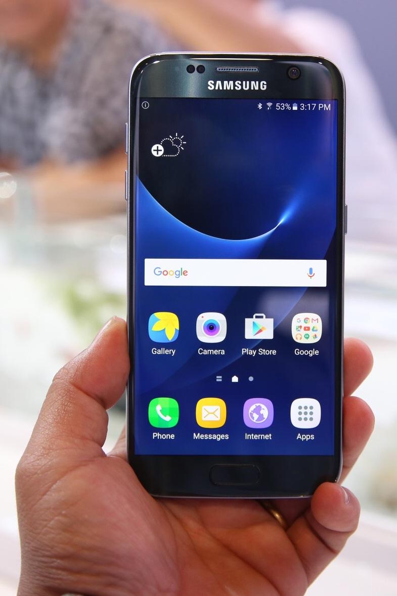 """Trên thực tế Galaxy S7 có độ dày hơn """"người tiền nhiệm"""" so với  kích thước 143.4 x 70.5 x 6.8 mm của Galaxy S6. Galaxy S7 có kích thước là 142.4 x 69.6 x 7.9 mm. Dù dày hơn nhưng cảm giác cầm nắm Galaxy S7 chắc và ôm tay hơn Galaxy S6"""