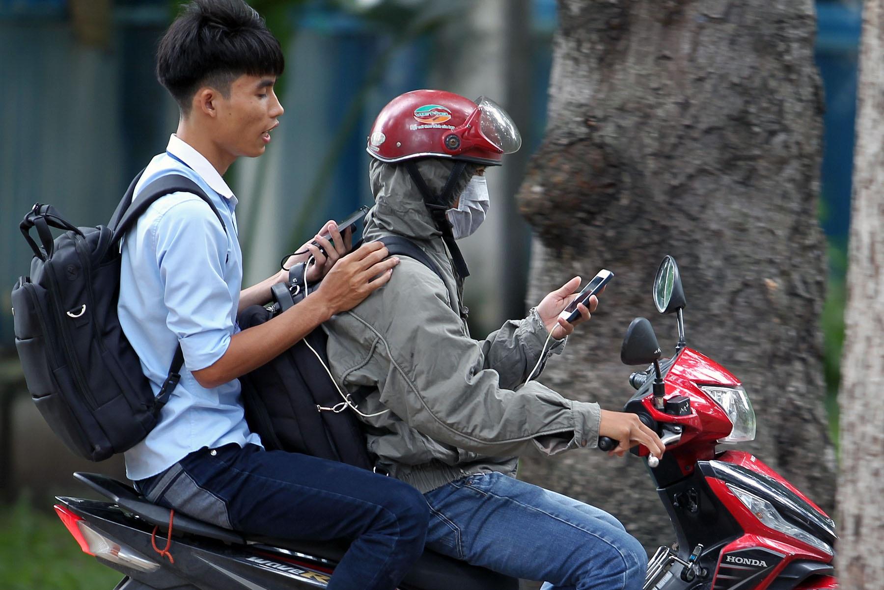 Cặp đôi chơi Pokemon Go dừng xe tại một công viên ở TPHCM. Ảnh: Nguyễn Quang