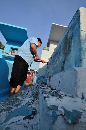 Người dân đang cạo lớp vôi bong tróc để chuẩn bị quét lại lớp vôi mới.