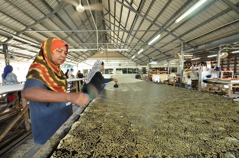 Thợ gia công vải Batik đang xử lý tạo hình mặt vải nhám.