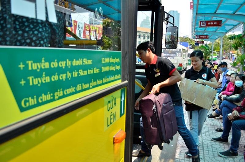 Xe buýt 109 đón khách tại trạm Bến Thành. Trong ảnh là phụ xe giúp hành khách chuyển hành lý lên xe.