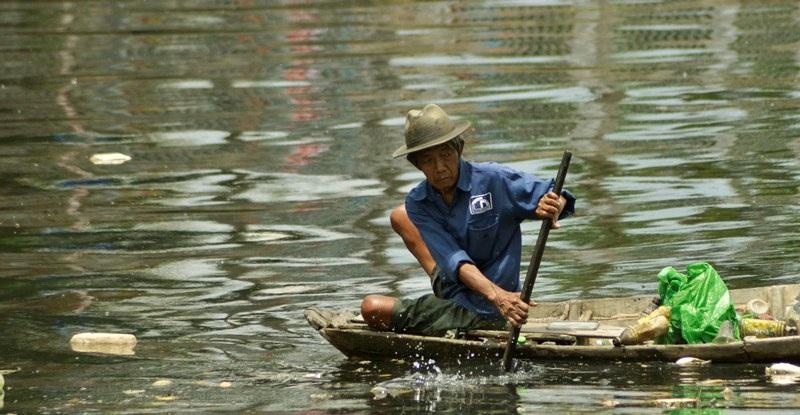 Bơi xuồng trên dòng nước đen ngòm, ông tranh thủ vớt thật nhiều ve chai, phế liệu.
