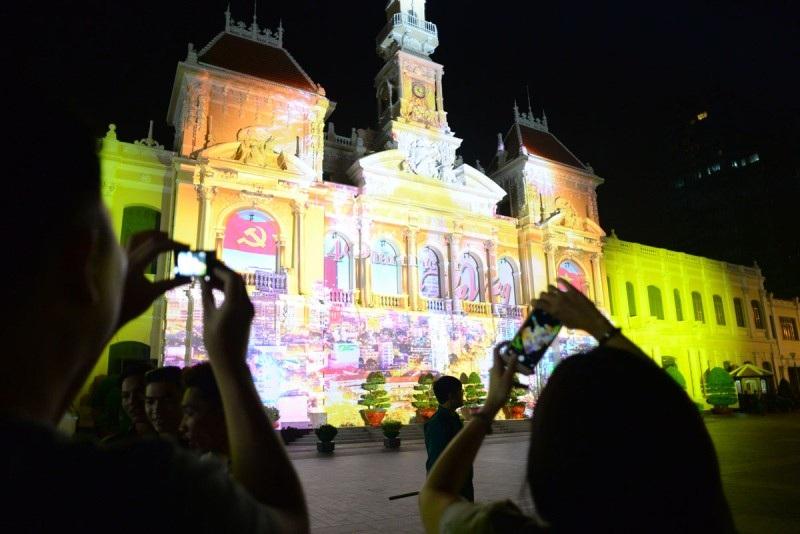 Người dân tranh thủ ghi lại hình ảnh chủ đề hiện trên toà nhà quen thuộc giữa trung tâm thành phố. ( ảnh: Nguyễn Quang)