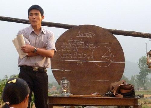 Cảnh thầy giáo Nguyên mang bảng gỗ đi dạy học cho học trò trên bãi cát trong Rừng chắn cát.