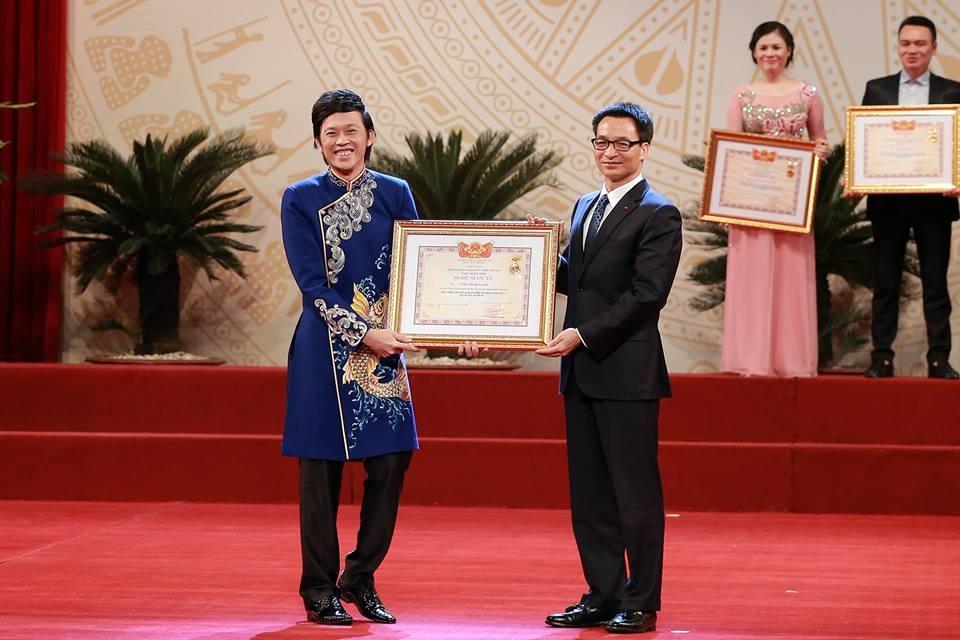 NSƯT Hoài Linh nhận bằng chứng nhận từ tay Phó Thủ tướng Vũ Đức Đam với nụ cười tươi rói. Ảnh: T.T.
