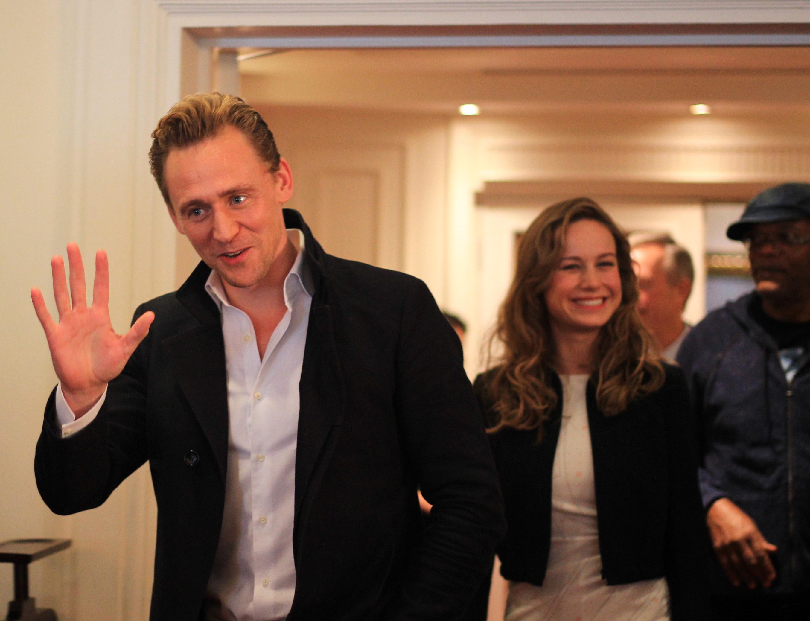 Tài tử Tom Hiddleston vừa bước vào phòng đã vẫy tay chào và nở nụ cười chết người. Đi sau anh là nữ diễn viên Brie Larson cũng cười rất tươi.