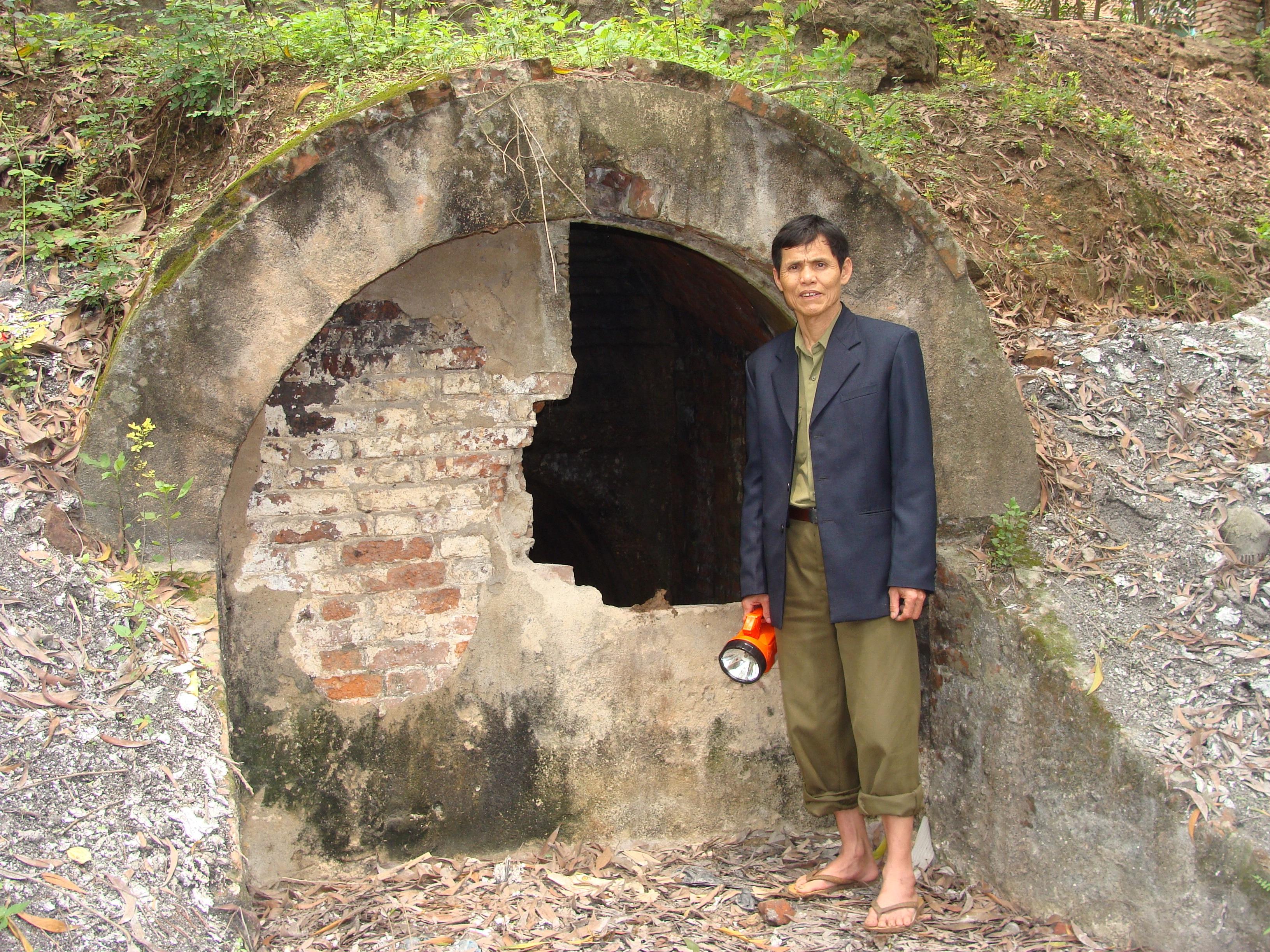 Ông Nguyễn Ngọc Thuỳ bên miệng đường hầm xuyên qua lòng núi phía sau đền thờ Bà Chúa Kho.