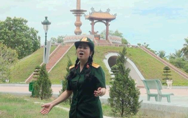 Nữ cựu chiến binh đứng bên Thành cổ để hát cho đồng đội nghe. Ảnh: T.A.