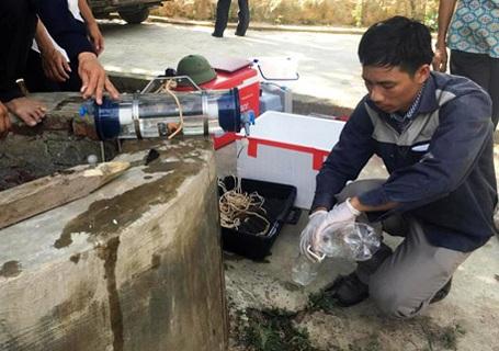 Đoàn công tác lấy mẫu nước tại giếng gần kề với bãi chôn chất thải trong trang trại của ông Lê Quang Hòa.