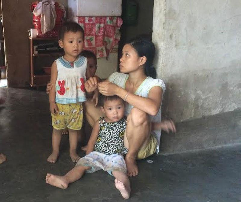 Chị Mến ngồi bệt bên 3 đứa con nhỏ nghe chúng tôi hỏi về việc gia đình có tiền mua đất ở mặt đường.