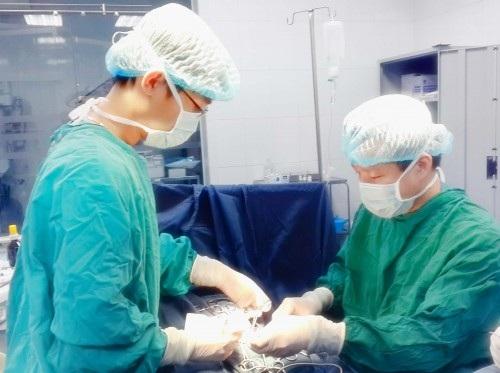 PGS.TS Trần Ngọc Sơn (bên trái) phẫu thuật cho bệnh nhi. Ảnh: BS cung cấp