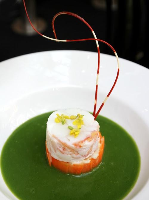 """Theo đầu bếp Vũ Văn Thành, các món ăn cũng như ý tưởng trình bày bàn tiệc, lấy cảm hứng từ """"cuộc thi ẩm thực"""" đầu tiên của Việt Nam - sự tích bánh chưng bánh giầy. Trong ảnh: Súp gạo rau bồ ngót với tôm hùm. Màu xanh thể hiện cho trái đất, phần tôm hùm nổi bật như trung tâm của vũ trụ."""