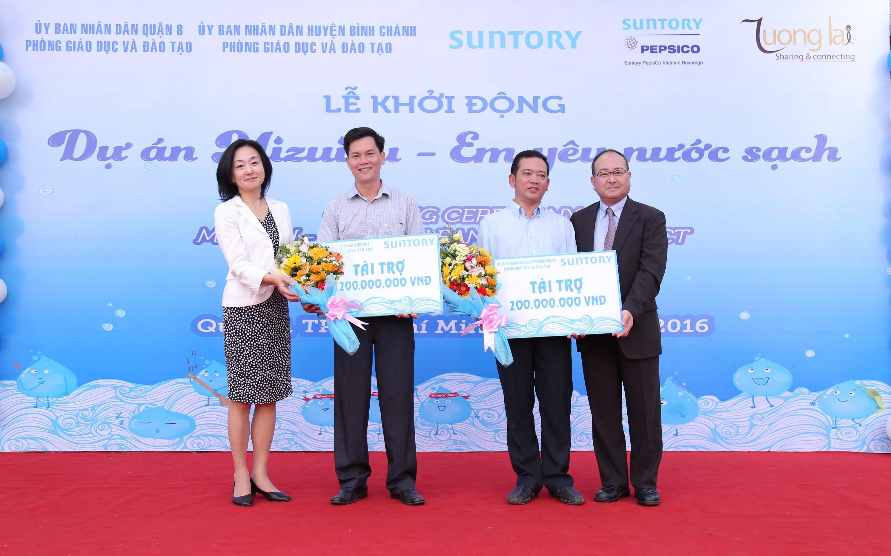 Đại diện Tập đoàn Suntory và công ty Suntory Pepsico Vietnam trao kinh phí hỗ trợ xây mới hệ thống lọc nước và nâng cấp nhà vệ sinh cho đại diện các trường tiểu học tham gia dự án