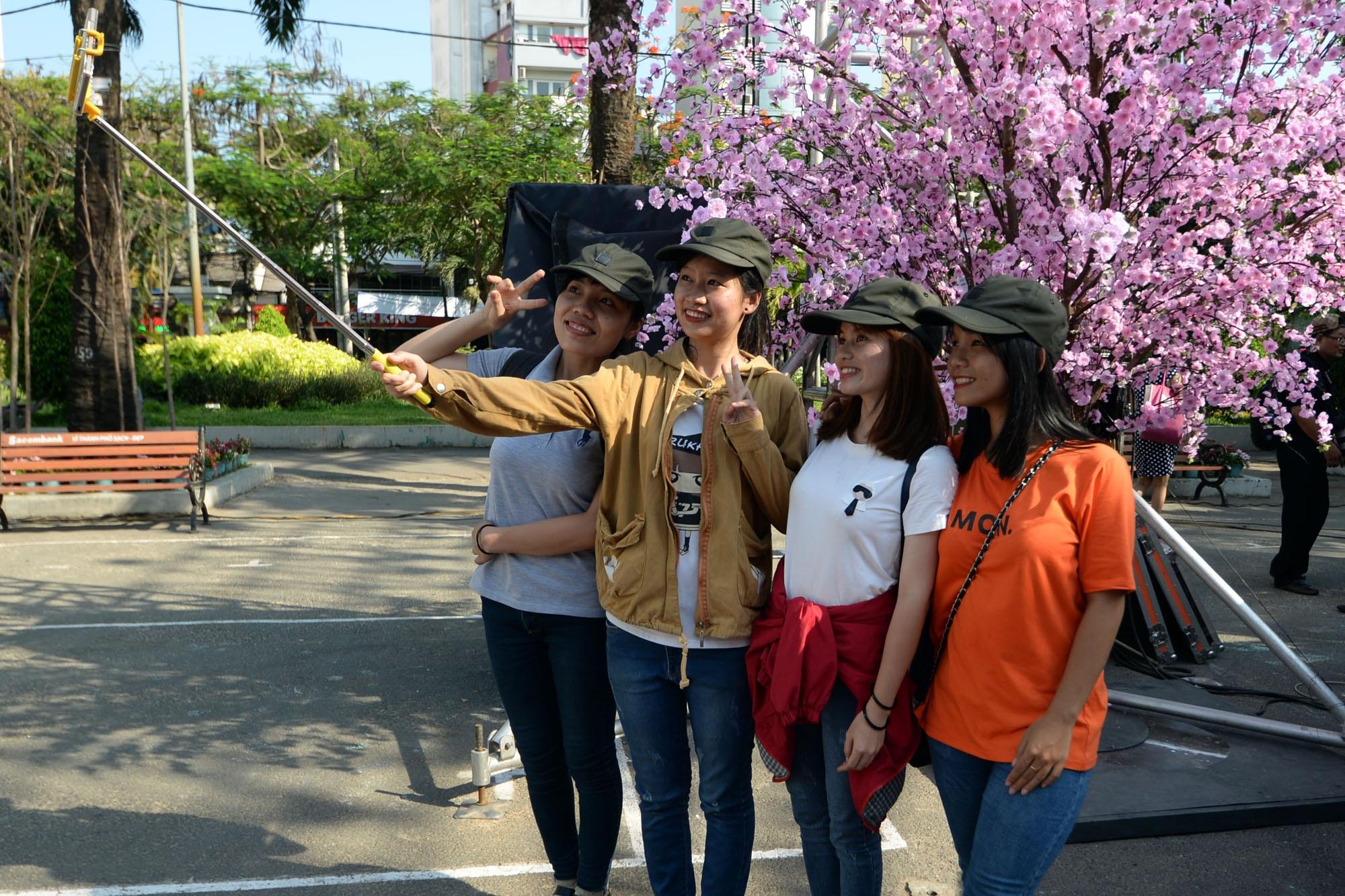Nhiều bạn trẻ tranh thủ cơ hội được chụp hình với hoa anh đào