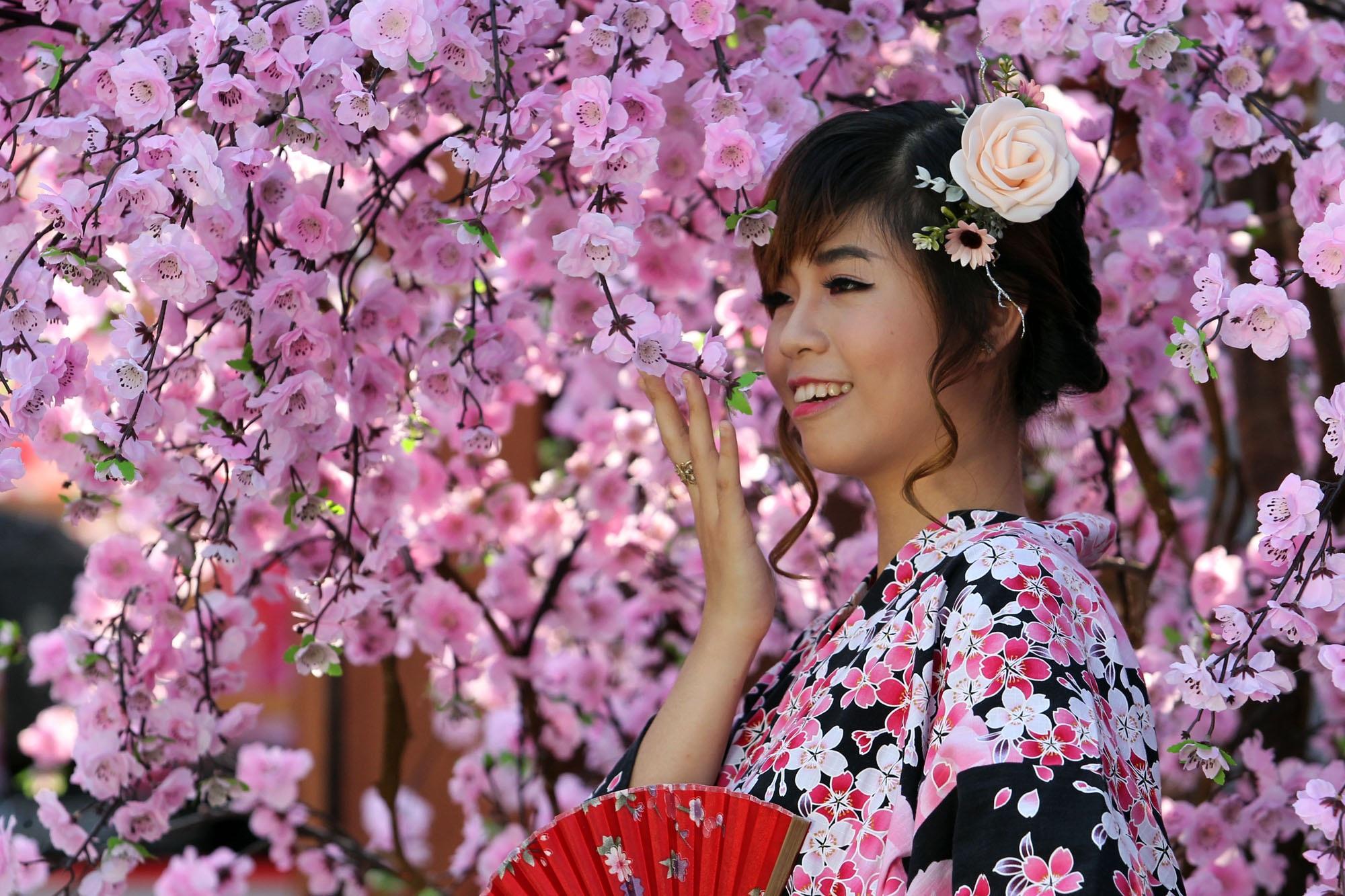 Có người mặc trang phục truyền thống của Nhật Bản để tạo dáng chụp hình trước hoa
