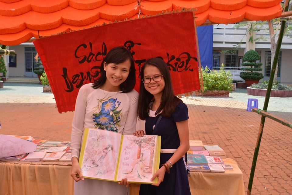 Cô Vũ Huệ (áo trắng) bên một tác phẩm của học sinh Phú Nhuận