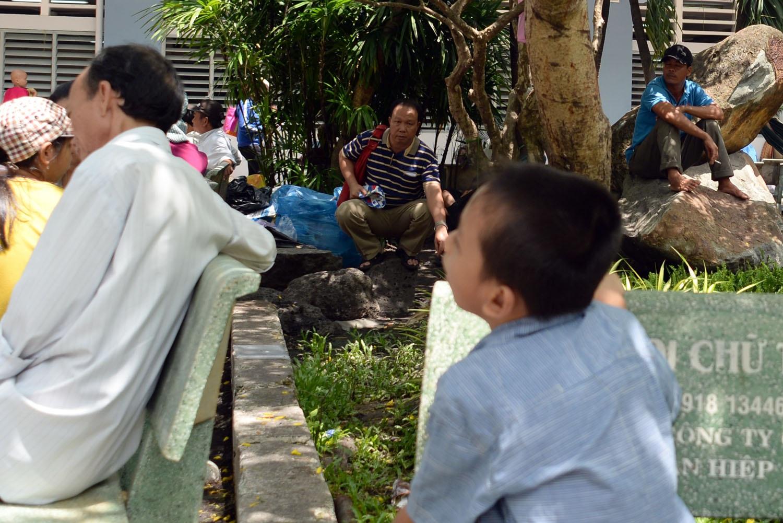Hai người đàn ông hút thuốc trước mặt một em nhỏ đang ngồi chờ khám bệnh