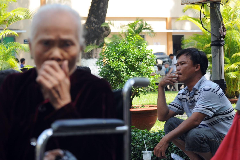 Bà cụ ho sặc sụa bên cạnh người đàn ông hút thuốc