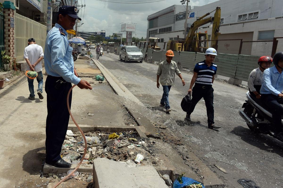 Để tránh bụi, bảo vệ cửa hàng kinh doanh liên tục tưới nước trên đường.
