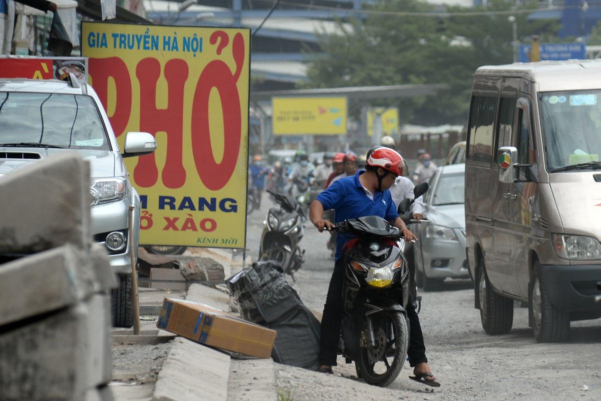 Người đàn ông chở hàng bị đổ xuống đường vì đường quá gập ghềnh