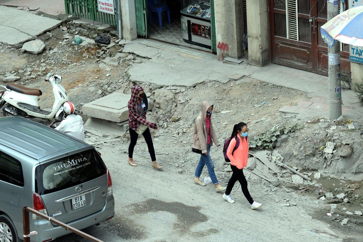 Những người đi bộ cũng phải đi xuống lòng đường để di chuyển vì vỉa hẻ lởm chởm