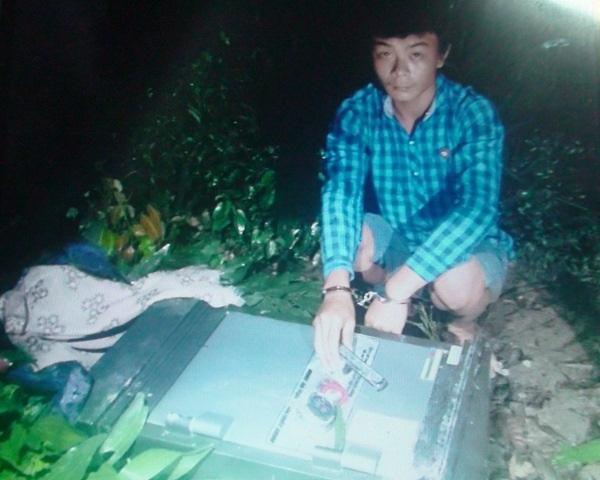 Hoàng Trọng Cảnh bên cạnh chiếc két sắt đã bị các đối tượng phá méo mó nhưng chưa lấy được tiền.