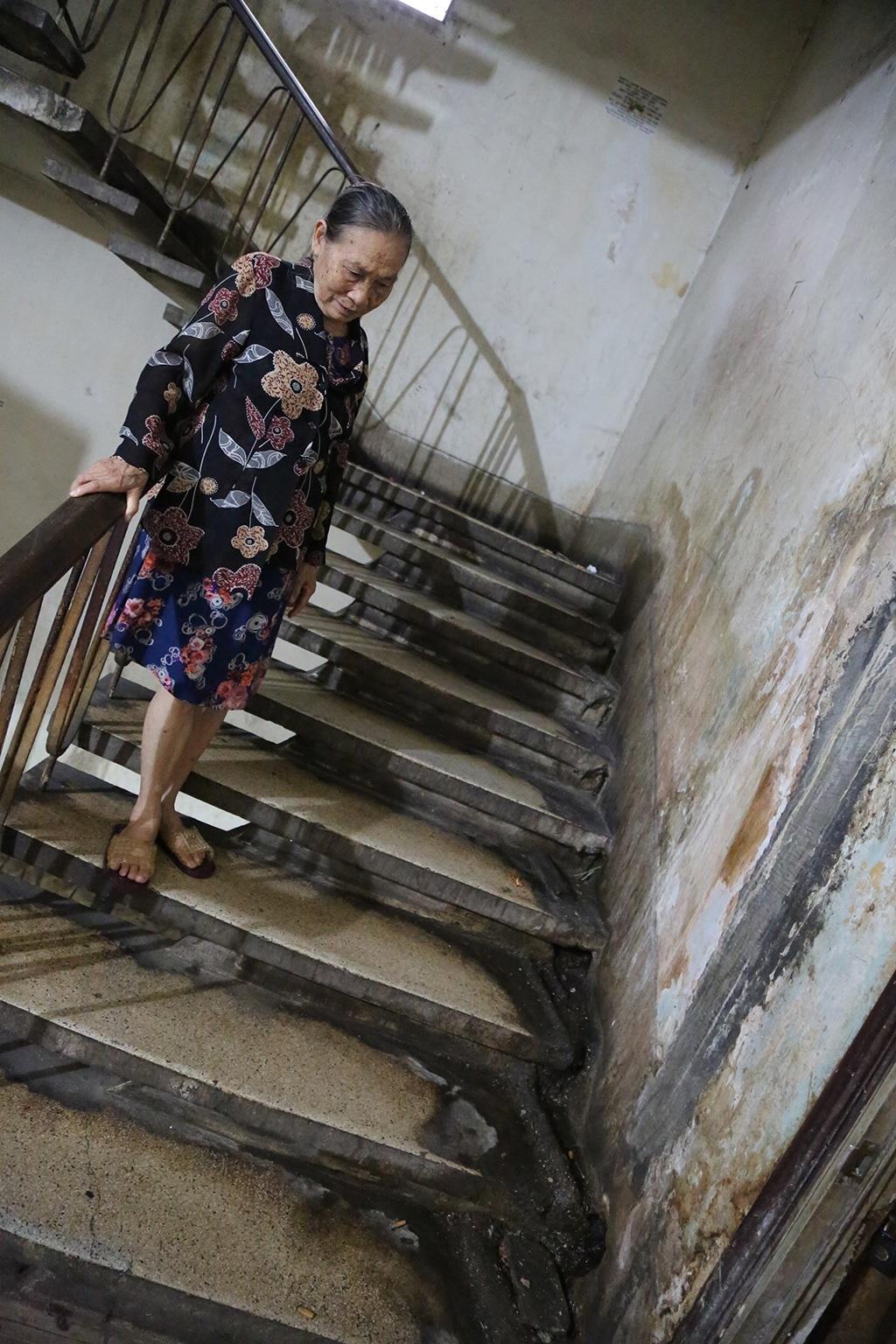 Bà Dục, cư dân sống tại chung cư số 9 đường công trường Lam Sơn chỉ nơi cầu thang bị rò nước khi trời mưa và ống nước âm tường rò rỉ bốc mùi hôi thối