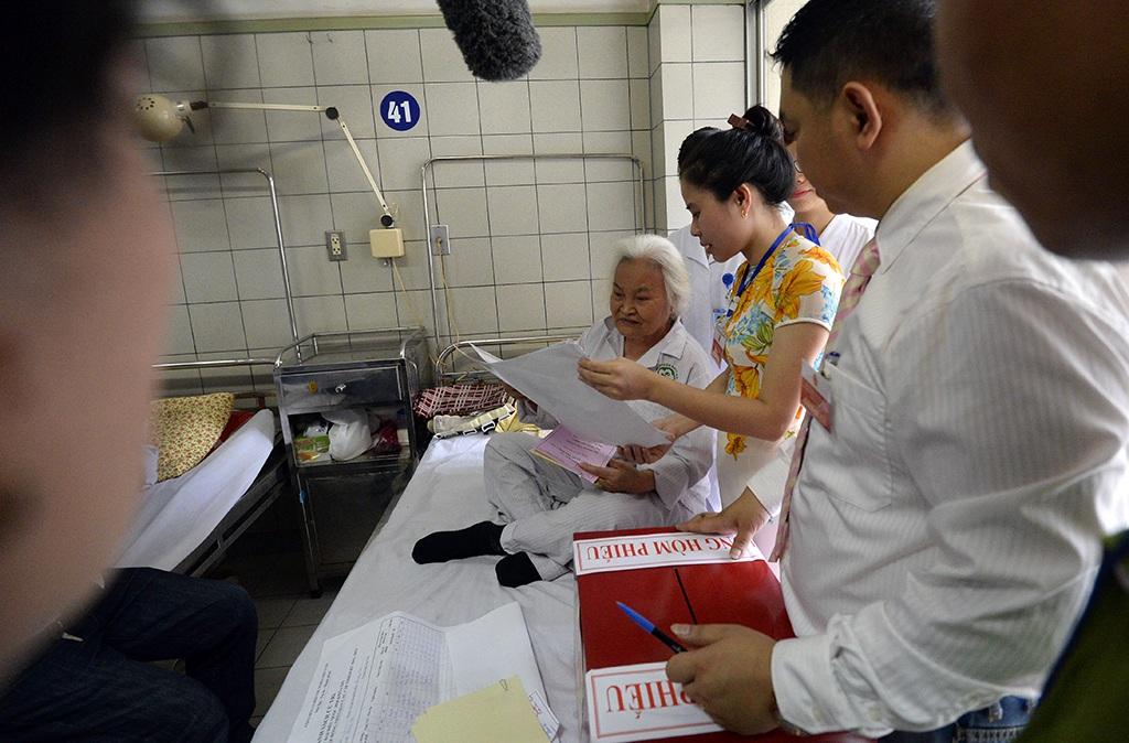 Cụ Nguyễn Thị Nga (SN 1937) ở Thanh Trì, Hà Nội được cán bộ trong tổ bầu cử lưu động đọc nghe trích ngang các đại biểu ứng cử.