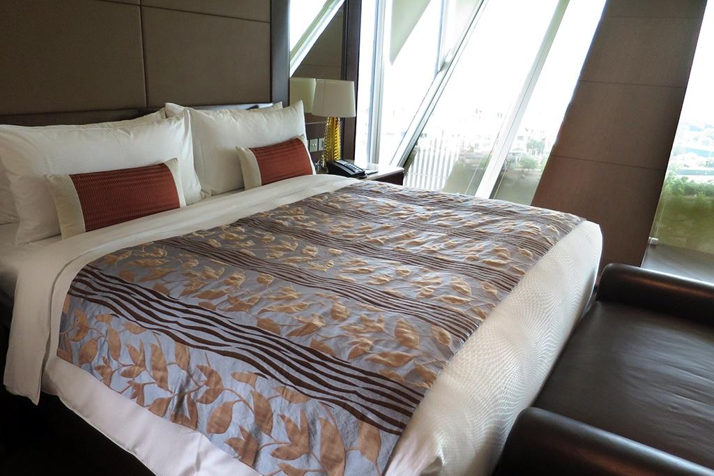 Giường ngủ tuân theo 3 gam màu chủ đạo của khách sạn: Trắng, đen và nâu đỏ sang trọng.