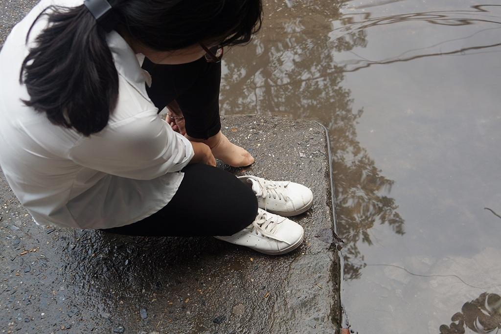 Người đến bệnh viên không tìm được đường đi, đành phải tháo giầy lội qua nước bẩn.