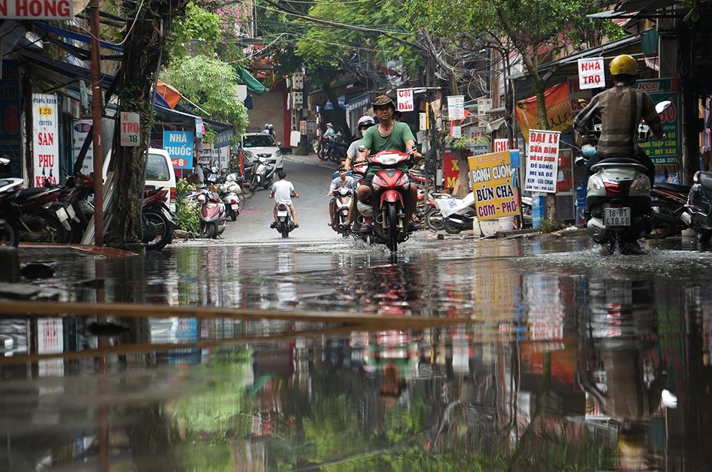 Những người bán hàng nước gần đó còn hóm hỉnh nói với phóng viên: Trời không mưa cũng phải mặc áo mưa. Vì mỗi khi sang đường gặp mấy anh đi xe thiếu ý thức là bị té ướt sũng nước cống bẩn.